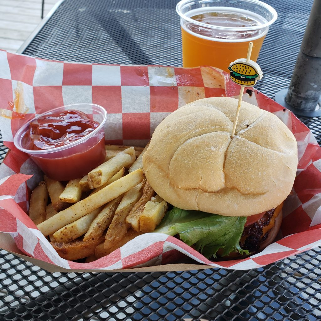 Cheeseburger with fries in a basket and beer